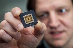 Professor Harald Haas holds a Li-Fi microchip processor